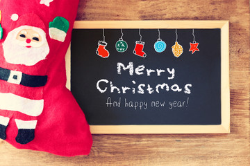 red sock and blackboard with merry christams greeting and colorf