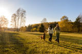 Couple walk dog in countryside autumn sunset