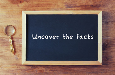 Top view of blackboard with the phrase uncover the facts written