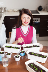 Happy brunette woman working with various seedlings