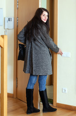 Woman in coat leaving the house