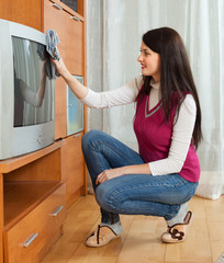 Brunentte woman wiping the dust  on TV