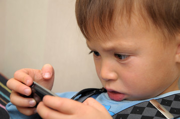 child playing on smartphone lying