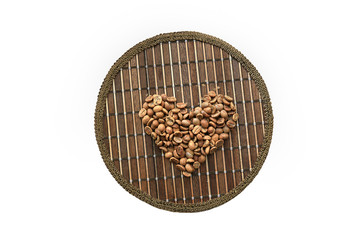 Heart of coffee beans on a round matting isolated