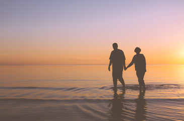 Senior couple walking at sunset