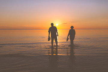 Senior couple strolling at sunset