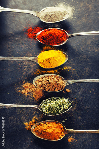 Colorful spices in metal spoons - 70202395