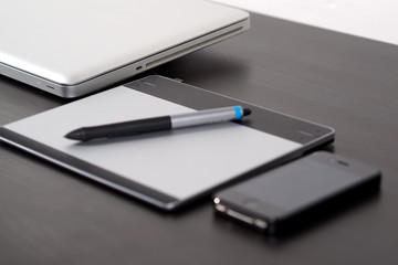 Graphic tablet on the table with notebook.