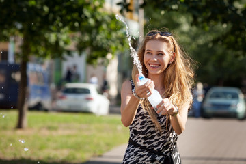 cheerful girl squirting water from a bottle