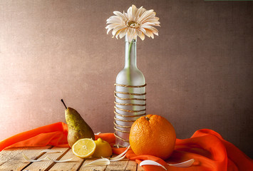 Still life white gerbera bottle fruits