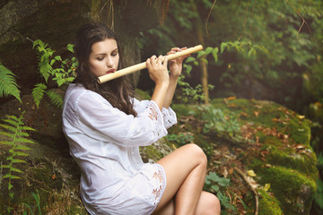 Beautiful woman playing  flute after the rain