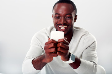 Portrait of a laughing african man using smartphone