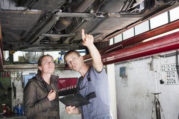 mechanic showing problems with car to client