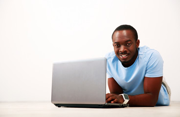 Portrait of a happy african man lying on the floor with laptop