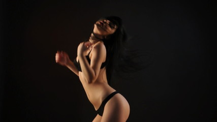 Sexy brunette woman in black lingerie dancing in the dark
