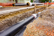 Newly laid pipe in a fresh trench. Unfinished pipeline - 70204532
