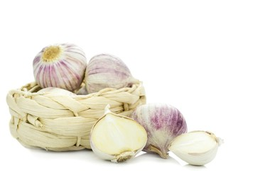 A group of pink garlic bulbs in a basket on a white background