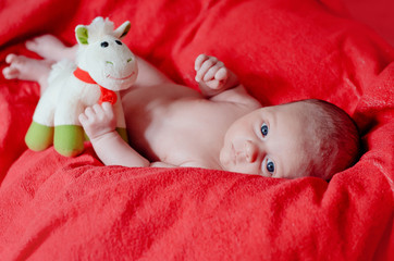 baby on red blanket