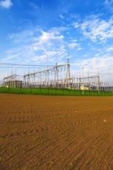 High voltage power transformer substation, field, blue sky