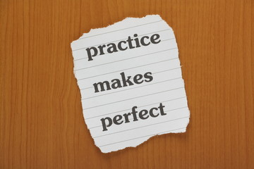 Practice Makes Perfect reminder note on a wooden background