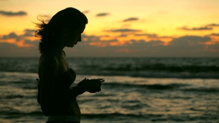 girl with phone on the beach