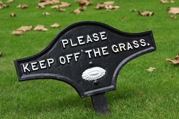 Please Keep Off The Grass sign on a manicured lawn