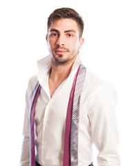 Male model with open collar shirt and two neckties hanging.