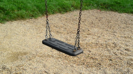 Empty swing seat swaying at playground in the park. 1920x1080