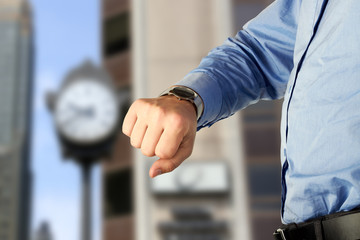 businessman checking time on his watch. Modern city behind