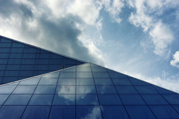 The glass panels of a building with reflection of clouds