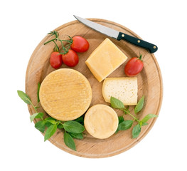 Cheeseboard with tomatoes, herb basil, isolated on white
