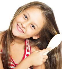 pretty smiling little girl brushing her hair isolated on white b