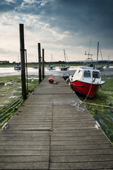 Landscape image of boats mored to jetty in harbor during Summer