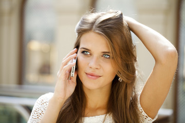 Portrait of a beautiful young woman calling by phone