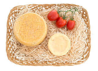 Cheese basket with red tomatoes over white background.