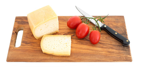 Sliced cheese on wooden board wth knife, isolated on white.