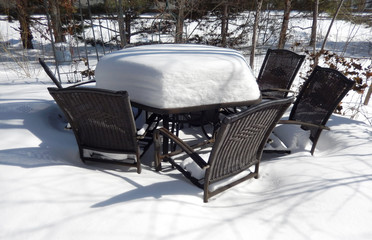 Backyard patio and outdoor furniture covered in winter snow