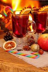 Christmas mulled wine - two glasses on the background of a burni