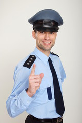 Smiling policeman shows with his finger on you