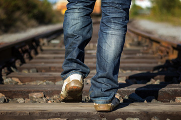 Closeup of person's feet walking on railway tracks