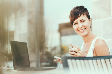 Young business woman with laptop in coffee shop