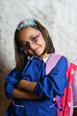 Scolara con zaino e grembiule primo giorno di scuola