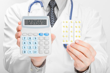 Doctor holdling calculator and pills in his hands