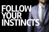 Follow your Instincts written on a board poster