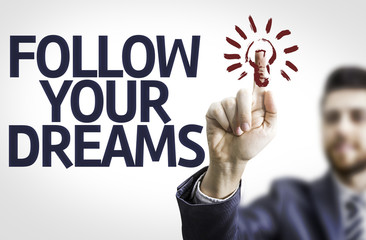 Business man pointing the text: Follow your Dreams