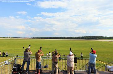 Fünf Fotografen halten ihre Kamera in die Luft auf leeren Himmel