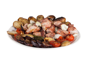 kebab and grilled vegetables on a plate isolated on white backgr