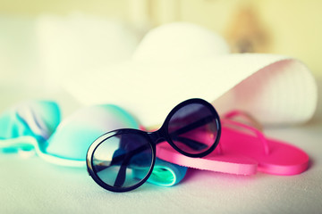 bikini top, hat, flip-flop and sunglasses