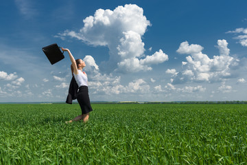 woman with a briefcase walking on the grass