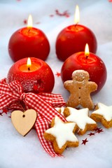 vier rote Adventskerzen mit Zimtsternen